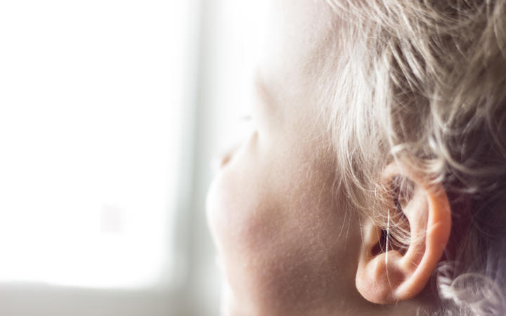 A young child looks out a window
