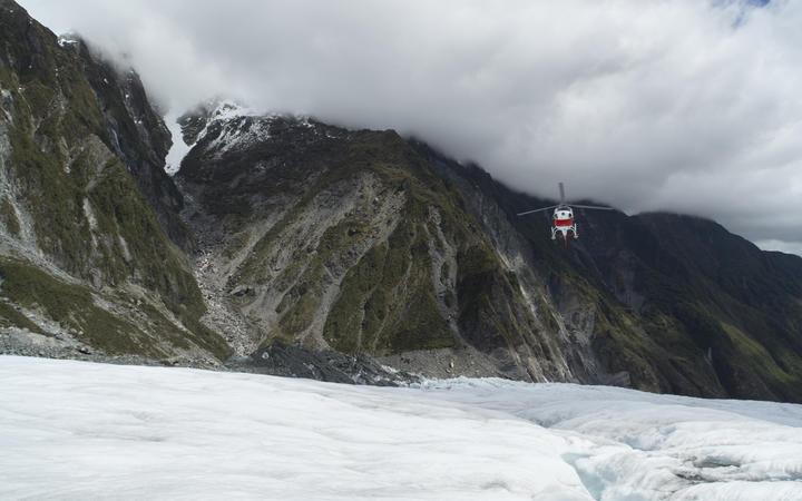 Helicopter landing on Franz Josef Glacier, South Island.
