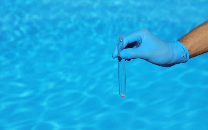 Man holding test tube with water against swimming pool on sunny day.