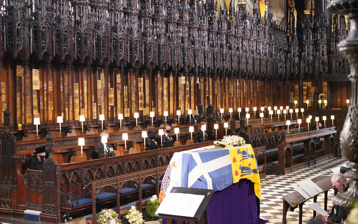 The Queen sits alone on the left during the funeral service for Prince Philip in St George's Chapel at Windsor Castle.