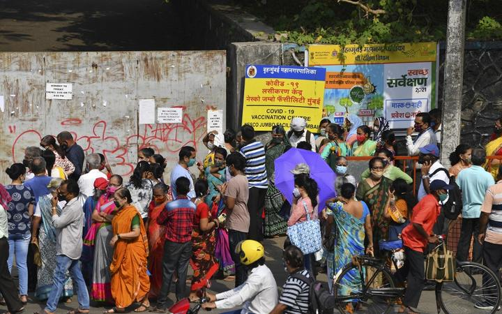 People gather outside an entrance gate of a Covid-19 coronavirus vaccination centre in Mumbai on April 28, 2021. (Photo by INDRANIL MUKHERJEE / AFP)