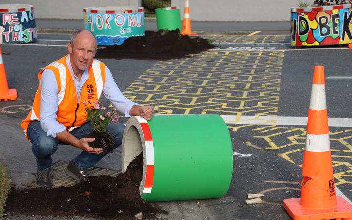 en7Streets.Jpg Up turned...Gore District  Council roading manager  Peter Standring rescues  plants that were buried in  soil when a planter pot  was overturned on the  corner of Ardwick and  Preston streets on  Monday night.