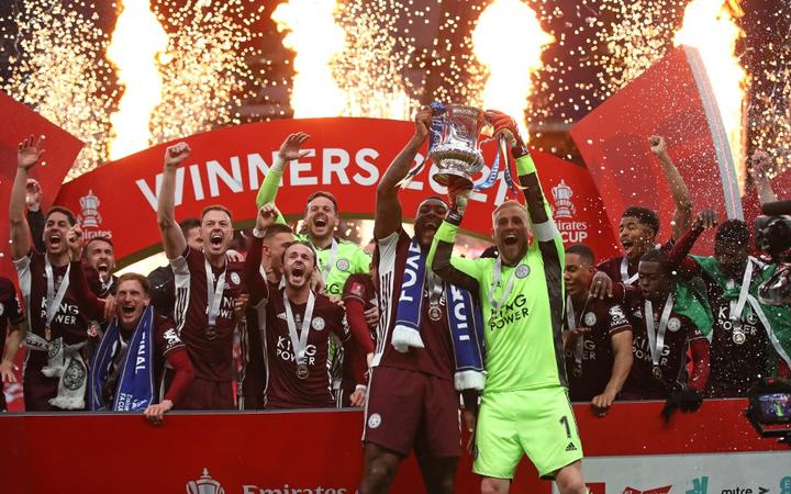 Leicester City's Jamaican defender Wes Morgan (L) and goalkeeper Kasper Schmeichel (R) hold up the winner's trophy as the Leicester players celebrate victory after the English FA Cup final football match  at Wembley Stadium May 15, 2021.