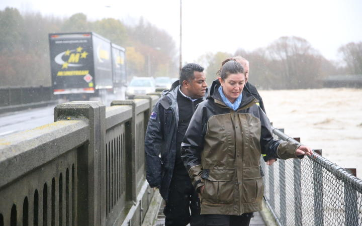 Labour Rangitata MP Jo Luxton looking at flood waters from the Ashburton State Highway 1 bridge, alongside Acting Minister for Emergency Management Kris Faafoi.