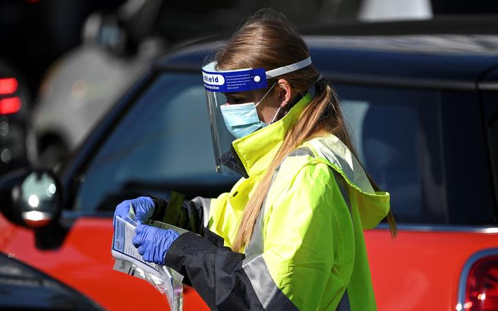 A health worker registers a resident at a Covid-19 coronavirus drive through testing site on Bondi Beach in Sydney on June 17, 2021,