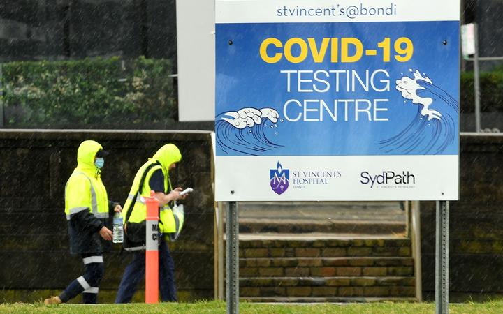 Medical officers walk past a sign board of Covid-19 testing center on Bondi Beach in Sydney on May 6, 2021.