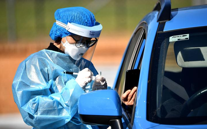 A health worker takes a swab sample at a Covid-19 coronavirus drive through testing site in the Smithfield suburb of Sydney on August 12, 2021.