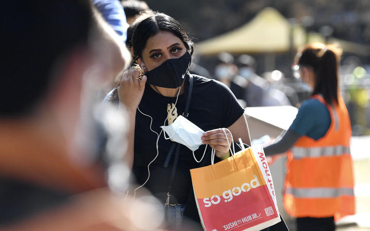 A woman stands waiting to get vaccinated in Sydney.