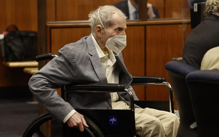 Robert Durst in his wheelchair spins in place as he looks at people in the courtroom.