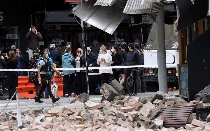 Residents gather near a damaged building in the popular shopping Chapel Street in Melbourne on September 22, 2021, after a 5.8-magnitude earthquake.