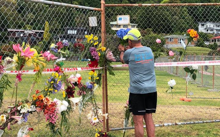 A local man places flowers from his garden on the Whakatāne boat ramp cordon.
