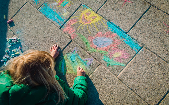 Child drawing outside on footpath with chalk.