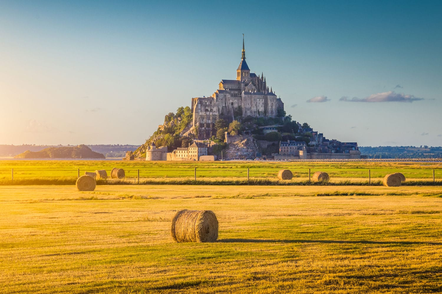 Beautiful view of famous historic Le Mont Saint-Michel tidal island in beautiful golden evening light at sunset in summer with hay bales on empty fields, Normandy, northern France