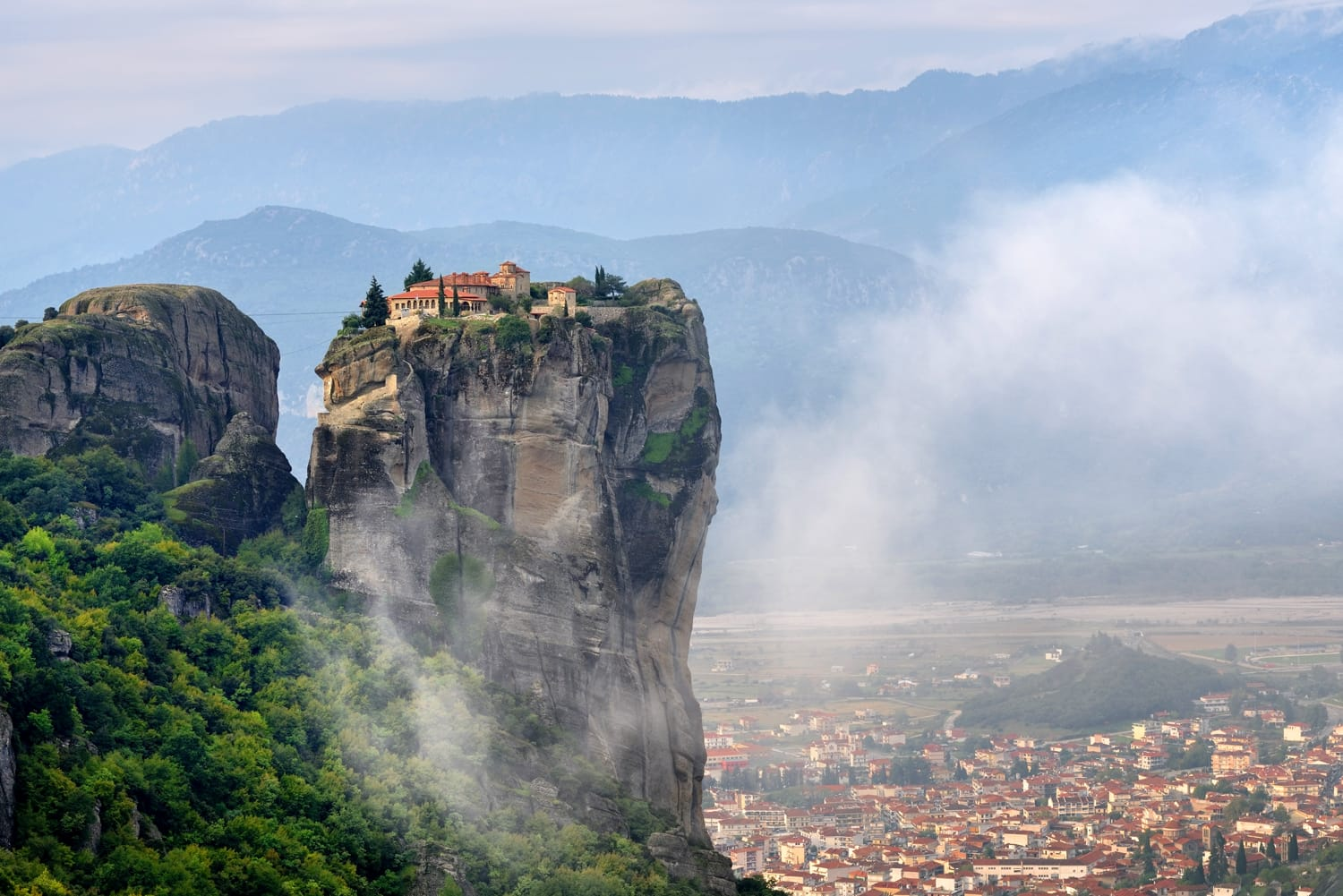 Meteora monasteries. Beautiful view on Monastery of the Holy Trinity placed on the edge of high rock covered of the morning at sun rises, Kastraki, Greece