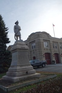 Statue of a fire fighter in front of the fire station