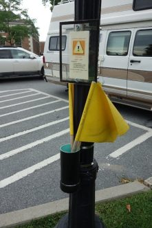 Pedestrians are encouraged to wave a yellow flag at oncoming traffic when they cross this street