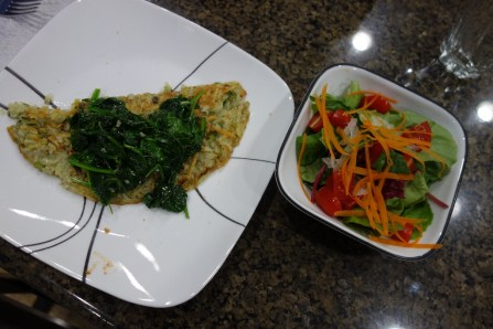 Potato pancake with spinach and a side salad