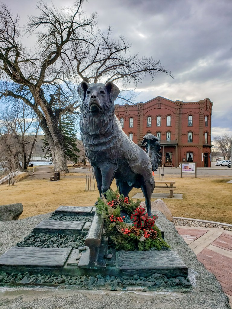 A statue of a dog with flowers. Behind is a red brick hotel