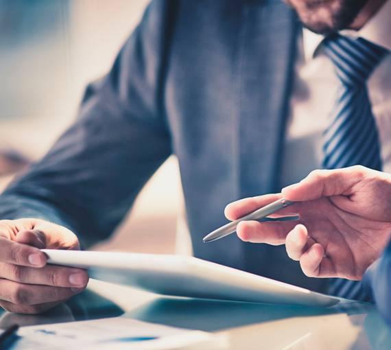 Brindes para empresas: empresários assinando documentos.