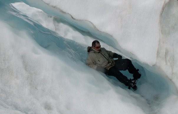 Sliding down an ice tube on Franz Josef glacier, New Zealand - Rob Gregory Author
