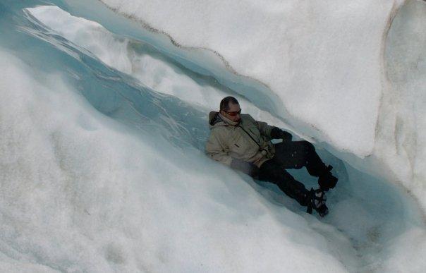 Sliding down an ice tube on Franz Josef glacier, New Zealand - Rob Gregory Author