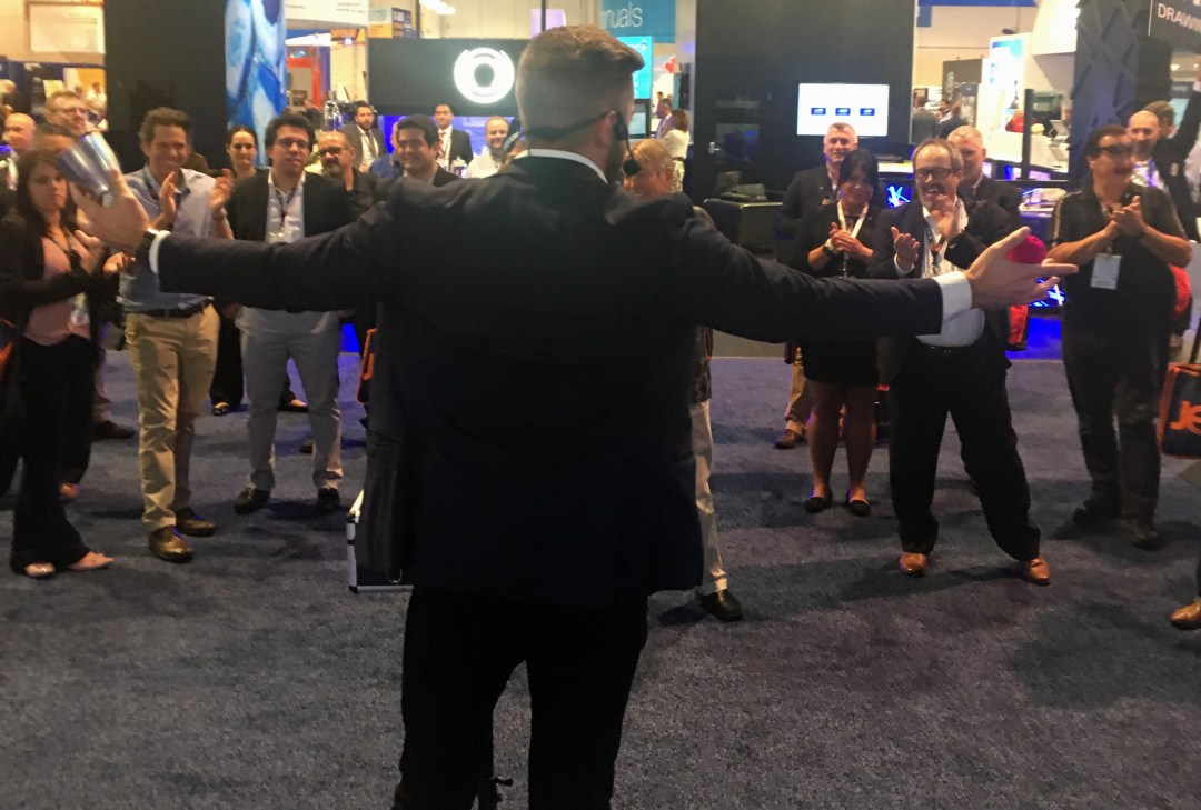 Trade Show Magician Rob Anderson performs at a clients booth at an airline trade show as a crowd of attendees applauds the performance.
