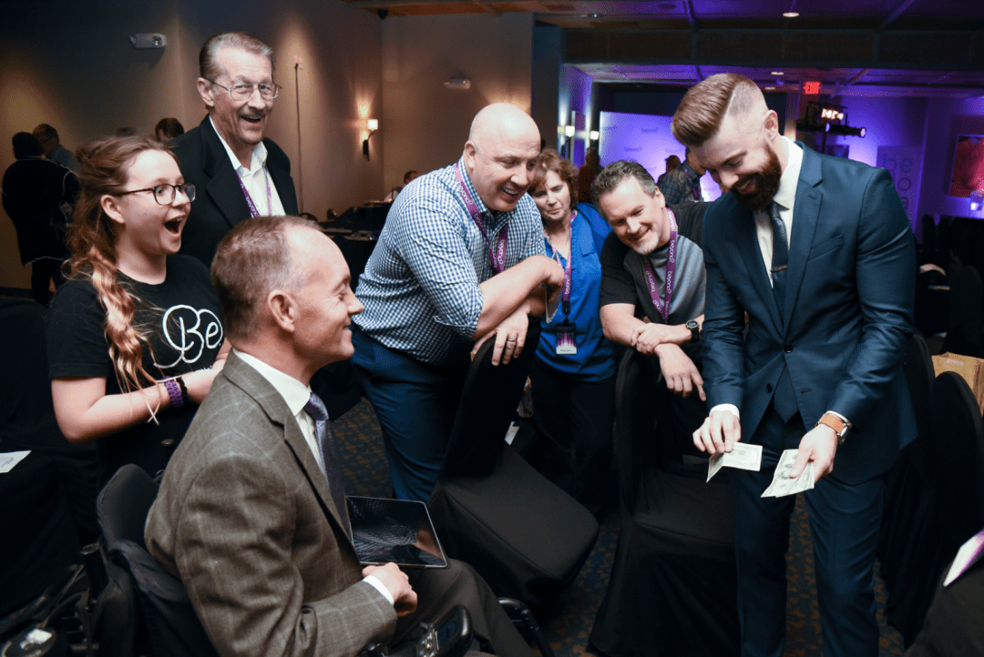 Las Vegas Corporate magician Rob Anderson performs strolling magic at a cocktail party as spectators react in amazement