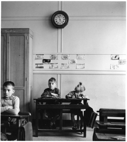 Three boys seated at desks in a 1956 classroom. One is looking up at the clock.