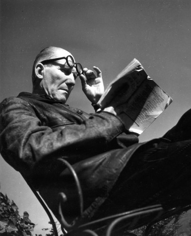 High sunlight and a low camera angle add drama to the image of a seated balding man, who with his left hand is lifting his glasses to read the book he is holding in his right.