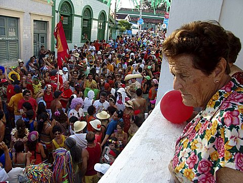 Brazil carnival. Crowd of revellers in the street during carnaval of olinda, pernambuco. Old lady looks on