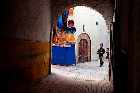 Children running through the streets of Essaouira medina, Morocco.