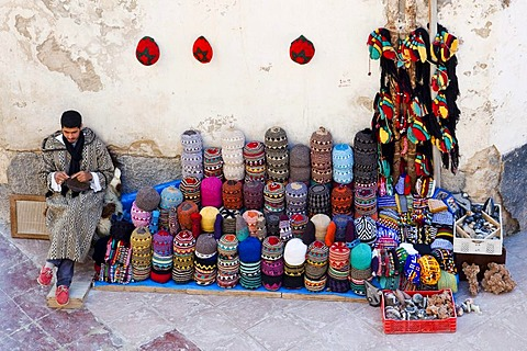 Man knitting and selling typical colourful Berber woollen hats in the historic town or medina, UNESCO World Heritage Site, Essaouira, Morocco, Africa