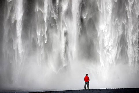 Man in red jacket standing in front of the 62m high Skogafoss waterfall near the village of Skogar, southern area, Iceland, Polar Regions