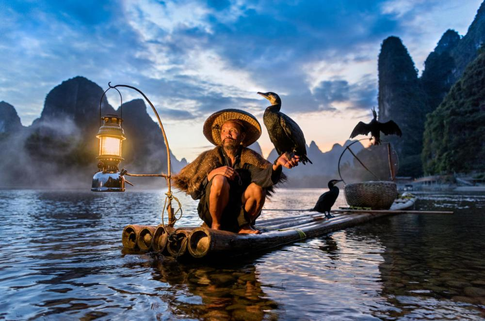 Fisherman with cormorant bird in Robdigphot