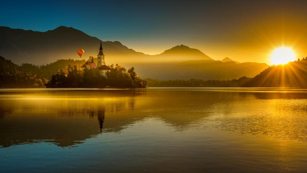 Hot air balloon over Lake Bled in the sunlight