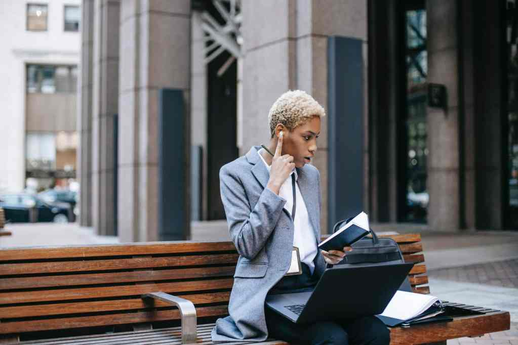 thoughtful female freelancer listening to boss calling with earphones
