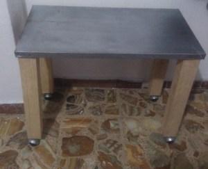 Mesa de trabajo realizada con un anaquel de acero y restos de un polín de madera. Se añadieron cuatro ruedas de un vieja silla secretarial.