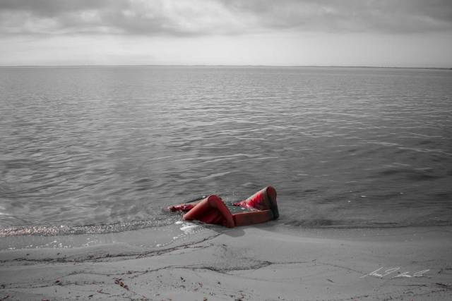 A red chair sinking into the sand on a beach.