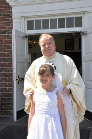 Reverend Stephen J. Madden poses with First Communion recipient Taryn Carol Powers.