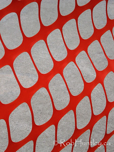Abstract image of an orange snow fence pattern against a concrete walkway.
