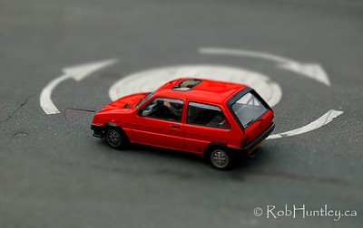 This red car is in a roundabout or traffic circle in Conwy, Wales. The shot was taken from the wall of Conwy Castle adjacent to the road.
