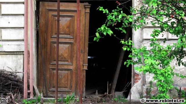 Un garaj amenajat într-o clădire veche din Cluj, cu o ușă dărâmată și una ruptă