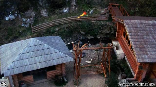 În curtea pensiunii Valea Paradisului din Măguri - Răcătău: foișorul (stânga), sala de mese (dreapta) și un pod peste pârâu