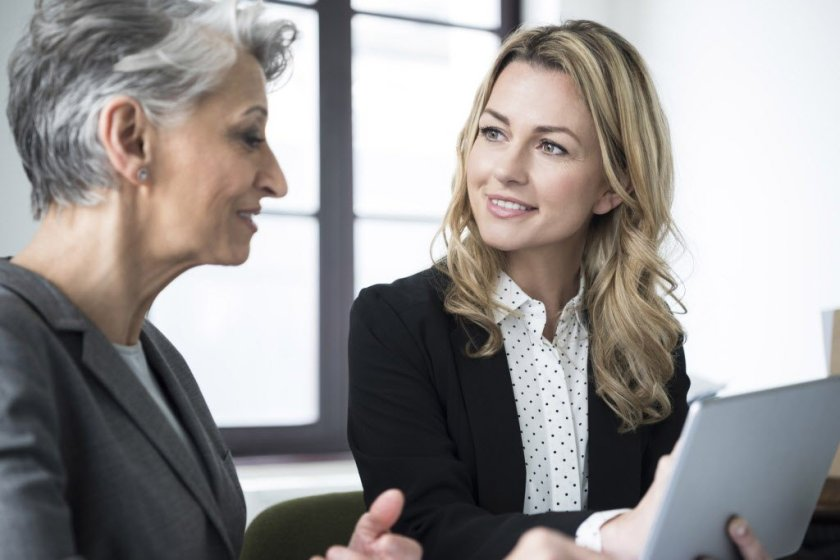 Stereotypical image of an older woman and younger woman in a business environment