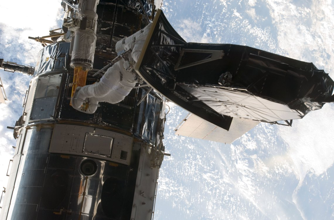 Image #5: But for the absence of gravity, astronaut Andrew Feustel, perched on the end of the remote manipulator system arm, would be a bit top heavy as he helps to install the Wide Field Camera 3 (WFC3) during a May 2009 spacewalk to upgrade the Hubble Space Telescope. Out of frame is veteran astronaut John Grunsfeld, his spacewalking crewmate. The pair kicked off five back to back days of extravehicular activity for the STS-125 crew. Credit: NASA