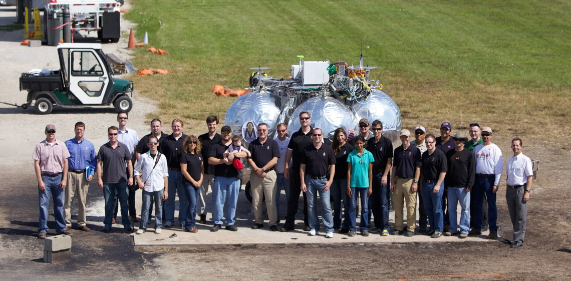 Members of the Project Morpheus team pose for a group photo during the 11th tether test of the prototype lander which took place in 2012 at the Johnson Space Center VTB Flight Complex. Credit: NASA/Joe Bibby