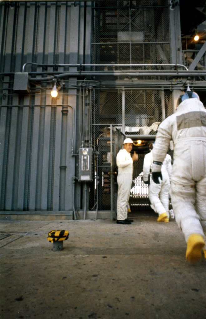 After having departed the transfer van at Pad 39A on launch morning, the crew prepares to board the first (ground level) elevator at the pad. They would soon transfer to a second elevator that would take them to the White Room at the 320 ft. level.