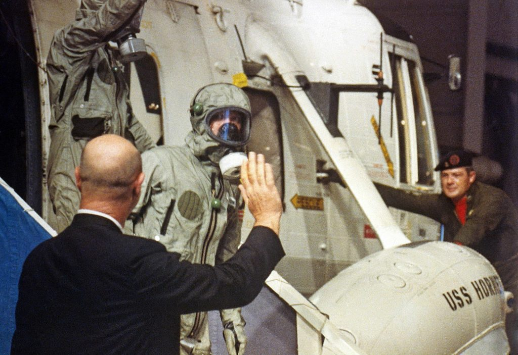 A member of the NASA recovery personnel waves to Apollo 11 crew (Michael Collins in front) as they depart the recovery helicopter aboard the USS Hornet.