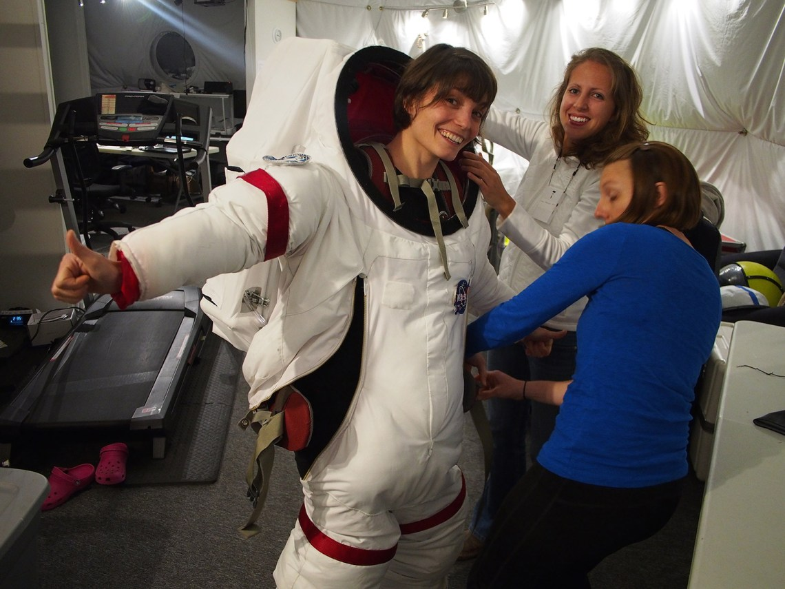 Lucie Poulet gets help suiting up for a EVA from her fellow crew members Annie Caraccio and Tiffany Swarmer.ccCredit: Ross Lockwood
