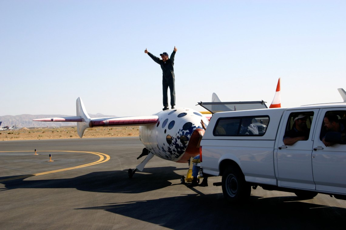 Mike Melvill celebrates atop SpaceShipOne (right) after completion of his first of two trips to outer space aboard the vehicle. Credit: http://www.flickr.com/photos/densaer/